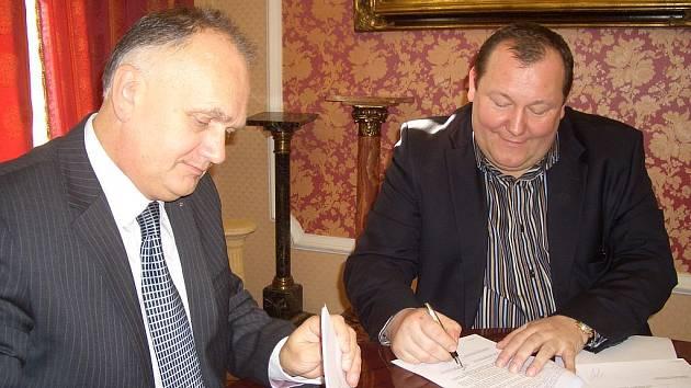 Historický podpis. Generální ředitel Becherovky Anthony Schofield (vlevo) a karlovarský podnikatel Karel Holoubek stvrzují 25. února 2009 podpisem smlouvu o prodeji historických objektů Becherovky v centru města ve prospěch Karla Holoubka.