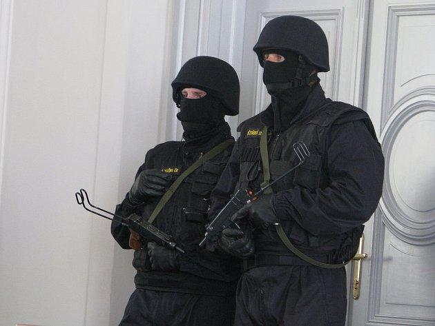 Policejní těžkooděnci hlídají vstup do soudní síně.