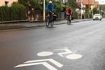 ZNAČKY PRO CYKLISTY na asfaltu řidičům aut i cyklistům připomínají, že po této silnici lze na kole překonat úsek, kde samostatná cyklostezka zatím chybí. Nově jsou po celé ulici Závodní.