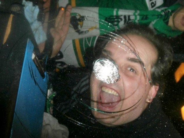 Odjezd fanoušků z Plzně zastavil letící kámen, který poškodil přední sklo autobusu. Prasklina dosahovala velikosti několika desítek centimetrů, jak předvádí Zdeněk Dobeš (v pozadí)