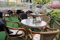 Prázdné stoly na restauračních předzahrádkách v lázeňském území.
