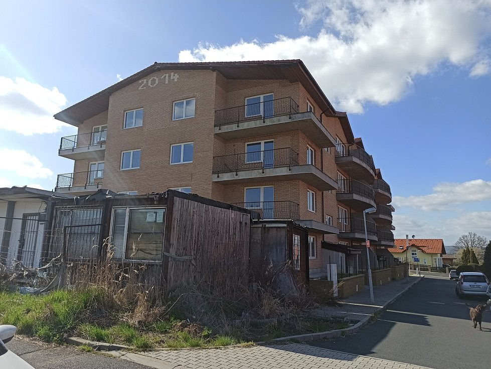 Čtyřpodlažní dům v Jenišově je vidět zdaleka, stal se nechtěným vředem obce. Areál zarostl, oplocení se rozpadá.