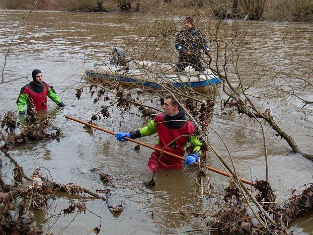 ŽABÍ MUŽI V AKCI. Policejní potápěči prohledávali celou neděli každou píď břehu Ohře pod zrádným jezem. Zjišťovali, zda se těla pohřešovaných vodáků nezachytila o kořeny stromů.