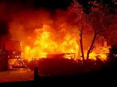 Chaty v rekreační oblasti zasažené požárem a zásah hasičů.