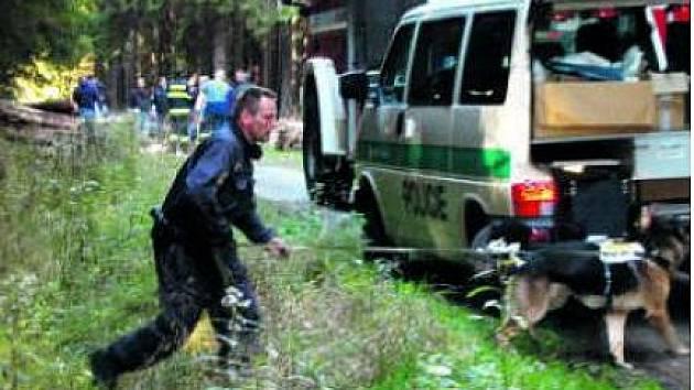 NĚKOLIK DESÍTEK POLICISTŮ včetně psovodů pročesávalo v pondělí les v okolí místa nálezu ohořelého lidského těla (u skupinky lidí v pozadí).