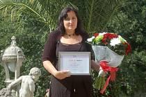 Hana Šimková s krásnou kyticí a certifikátem Žena regionu, před hotelem Richmond, kde jí bylo toto ocenění předáno.