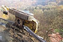 Na silnici č. I/13 u Stráže nad Ohří havaroval v pátek 29. října odpoledne tahač s bagrem. Ten při nehodě spadl s návěsu a zaklínil se nad dvěma domy.