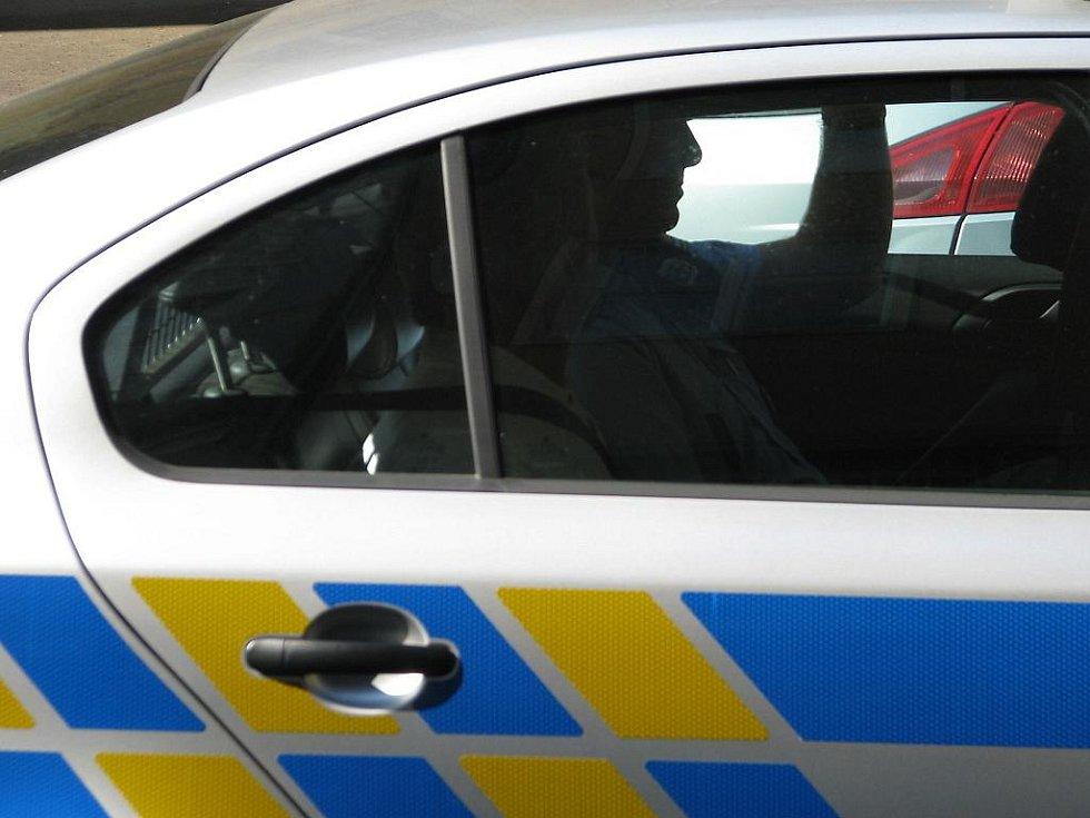Policisté přivážejí k výslechu muže, podezřelého z loupeže na poště v Tašovicích.