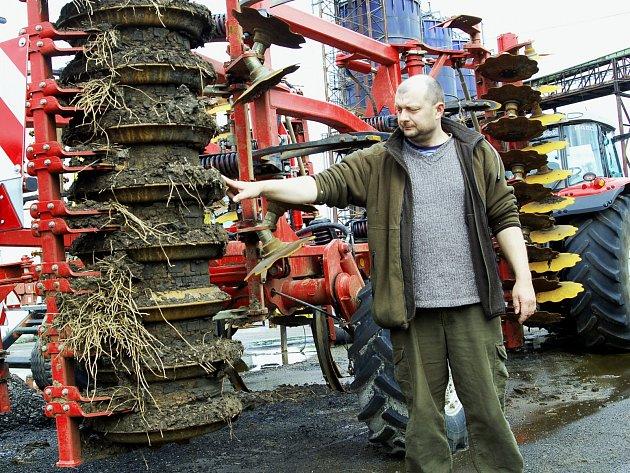 ŘEDITEL STATKU BOR Vladimír Matějů ukazuje nánosy bahna na strojích, které ztěžují práci zemědělcům.