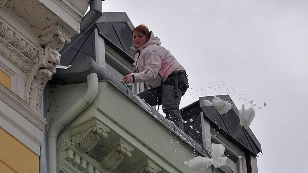Odstraňování rampouchů a sněhových převisů ze střech domů v na třídě T. G. Masaryka v centru Karlových Varů.
