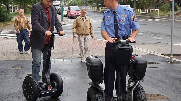 """Proti fyzikálním zákonům se zdá být jízda na dvoukolce Segway. Ovládání je přitom velice jednoduché. Zapůjčenou """"zbraň"""" si včera pod dohledem Jindřicha Láta (v uniformě) vyzkoušel i velitel karlovarských strážníků Marcel Vlasák."""