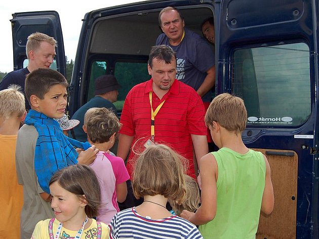 Jan Bureš (v červené košili), starosta Ostrova a poslanec parlamentu, ale také 'ten, co drží kasu' – hospodář letního dětského tábora v Manětíně.