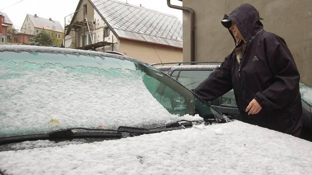 První sníh motoristům radost neudělal. Řada z nich ještě ani nepřezula auta na zimní gumy. Na snímku odklízí sníh z auta řidič v Kraslicích.