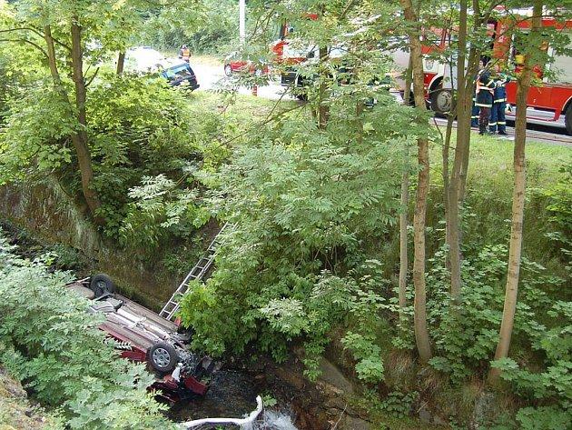 Srážka dvou automobilů v Jáchymově. Jeden z vozů po kolizi narazil do stromu, druhé auto se zřítilo do potoka.