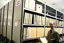 Archivář ukazuje jedny z mnoha plných šanonů, které byly naskenovány