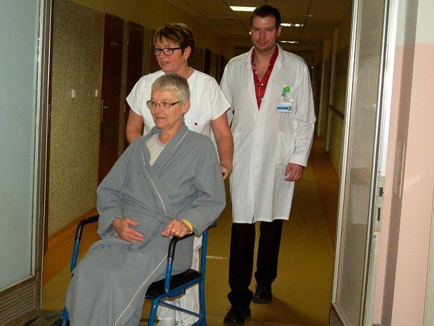 Pacientka Karlovarské krajské nemocnice Jiřina Olmrová se na vozíku vrací do svého pokoje. Z tiskové konference, kde tým lékařů včera prezentoval nový typ unikátní operace, ji doprovází sestra a primář urologického oddělení Jan Pokorný.