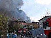 Hasiči zasahují u požáru haly na výrobu lepenky.