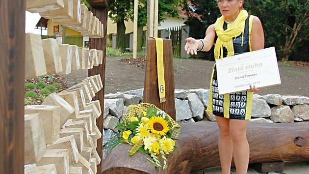 STAROSTKA Dolního Žandova Eliška Stránská ukazuje jedno z upravených míst v obci, prostranství nedaleko kostela se zázemím pro děti.