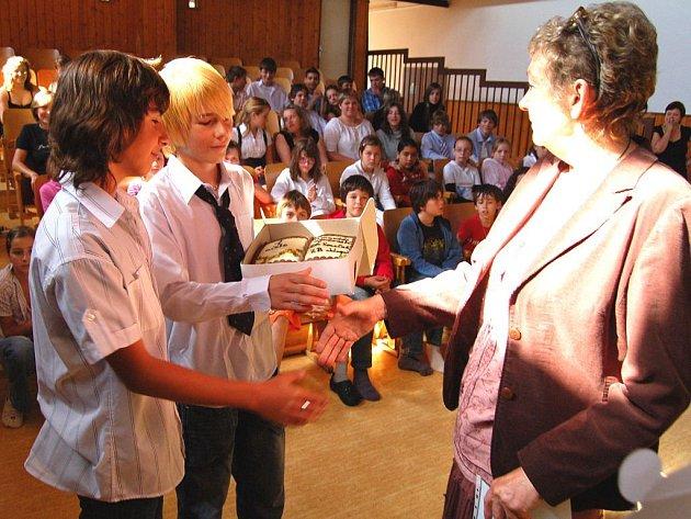 Sladkou odměnu pro absolutní vítěze 15. ročníku soutěže Kamarádi moudrosti převzali z rukou ředitelky Krajské knihovny Evy Žákové sedmáci David Oleksík (vlevo) a Roman Pásek.