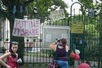 Demonstranti vyvěšují transparenty na plot konzulátu.