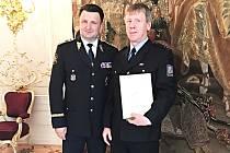 Oceněný policista Miroslav Kozák (vpravo) s vyznamenáním a policejním prezidentem Tomášem Tuhým.