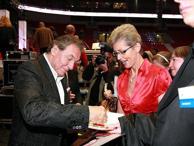 Karel Gott se v KV Areně podepisuje jedné z fanynek.