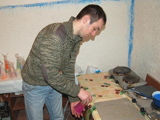 Pracovník karlovarského K-centra předvádí, jak klienti tohot zařízení vyrábějí svíčky. Tato práce je jedním ze tří hlavních bodů projektu STOP Vyloučení.