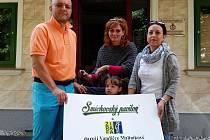 Martin Šretr spolu s ředitelkou denního centra Žirafa předávají šek Vandičce Maliníkové.