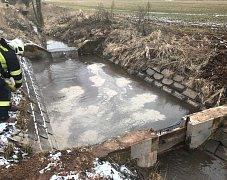 Okolí a voda znečištěná uniklým olejem.