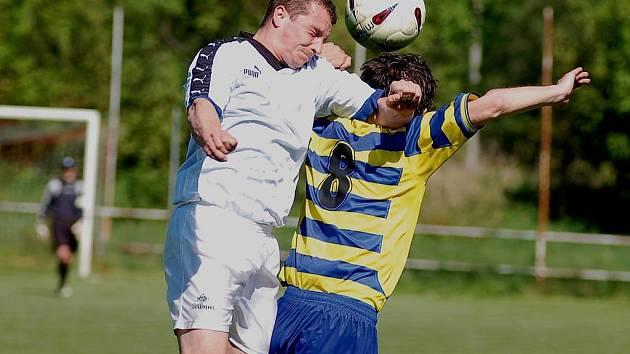Poříčský Štěpán Dubaj (v bílém) v souboji o míč.