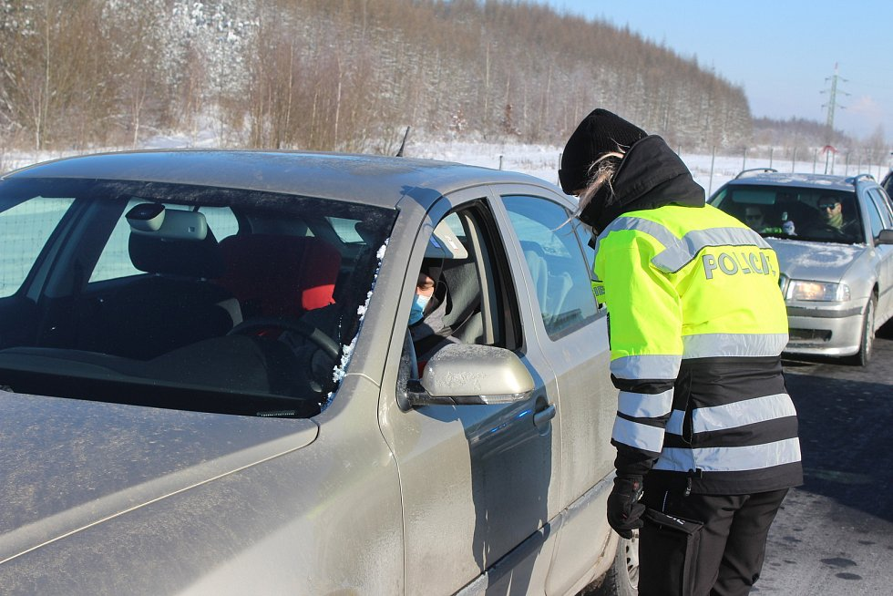 První den uzávěry okresů Cheb a Sokolov. Policisté kontrolují řidiče na D6 za obcí Hory.
