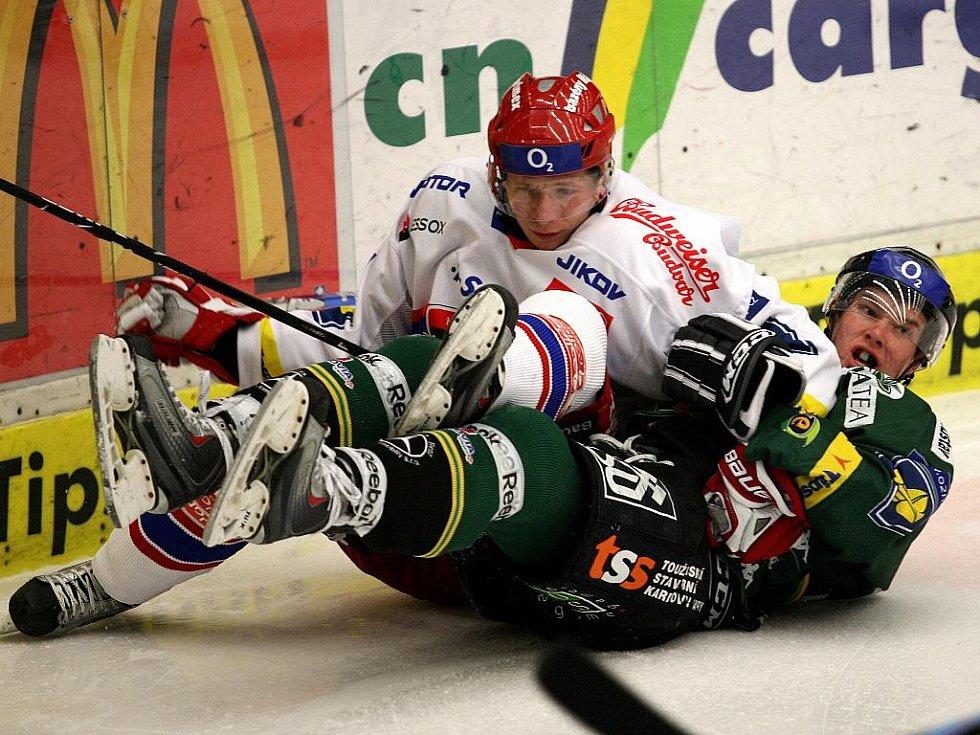 Hokejisté karlovarské Energie (v zeleném) prohráli v předehrávce 36. kola v Českých Budějovicích 0:4.Domácí útočník Tomáš Micka v souboji s Martinem Parýzkem.
