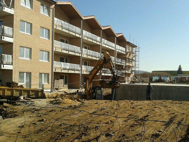 Na stavbě v Jenišově v pondělí klid nebyl. Bagr tady nakládal zeminu do náklaďáků.