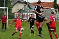 Votický kapitán Jakub Šlejmar (v červeném) odpaluje míč ve Vestci z vlastní šestnáctky.