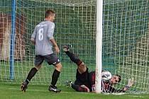 Votický Marek Slunečko kontroluje míč letící do zbuzanské sítě,  který již nestačil brankář Pavel Rams zachytit.