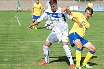 Benešovský stoper Zdeněk Hašek (ve žlutém) se snaží kousek od vlastního pokutového území odtlačit od míče kladenského Ladislava Vojtka.