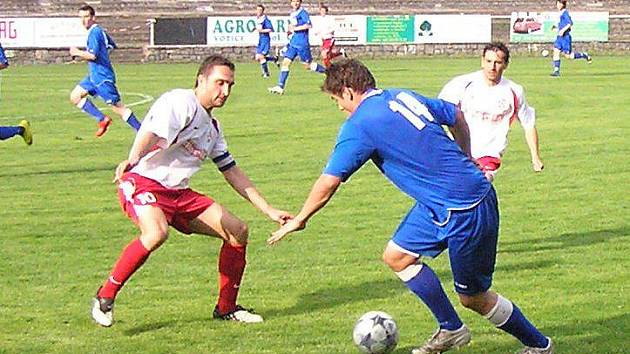 Třeboňský Tomáš Leština (v modrém) se snaží přejít přes domácího kapitána Michala Polodnu.
