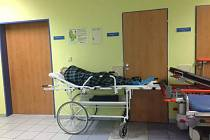 Pacientka na chodbě benešovské nemocnice čekající na odvoz domů.