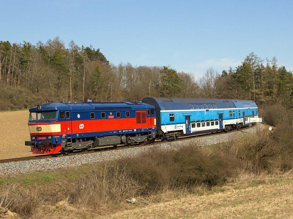 Osobní vlak 9057 na čele patrových vozů. Lokomotiva Zamračená či Bardotka 749 121-0 projíždí po trati 210 mezi zastávkou Pecerady a zastávkou Poříčí nad Sázavou Svárov.