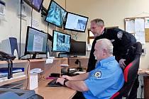 Velitel Městské policie Benešov Radek Stulík (v černém) před monitory kamerového bezpečnostního systému.
