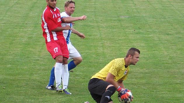 Před dotírajícím kácovským Červeňákem (v červeném, hlídán Barešem) lapil míč brankář Votic Tůma.