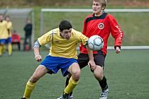 Benešovský starší dorostenec Patrik Vyhlídal (ve žlutém) hypnotizuje míč před příbramským hráčem.