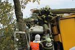 Popelářský vůz po srážce s dodávkou narazil do stromu, který museli benešovští hasiči vyvrátit pro vyproštění zraněného řidiče a závozníka.