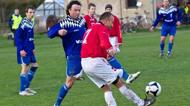 Zkušenost se potkala na hřišti. Nespecký Kamil Kulhavý (v červeném) centruje míč před hrajícím trenérem Chocerad Janem Kuželkou.