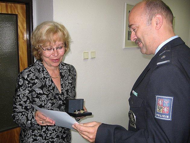 Velitel benešovské uniformované policie Milan Plachý předává diplom Blance Šantrůčkové, která resuscitovala dvanáctiletého chlapce při vážné dopravní nehodě u Poříčí nad Sázavou
