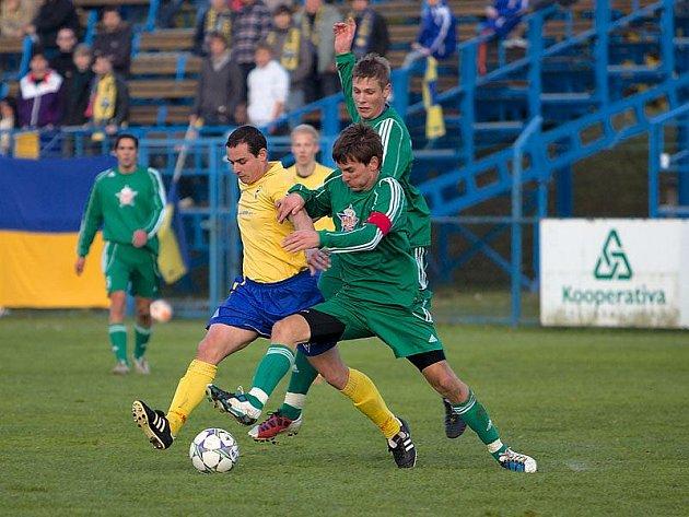 Ve středu hřiště se střetli v souboji kapitáni týmů - benešovský Martin Turek (ve žlutém) a tachovský Pavel Kaše.