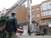 Plechy mohly ze střechy spadnout a ohrozit chodce. Hasiči tomu ale zabránili.