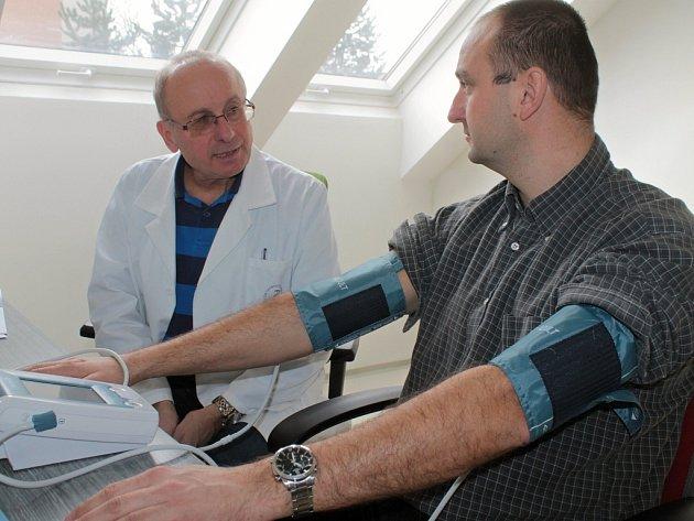 Lékař Jan Bruthans hovoří s Michalem Pechačem při měření tlaku.