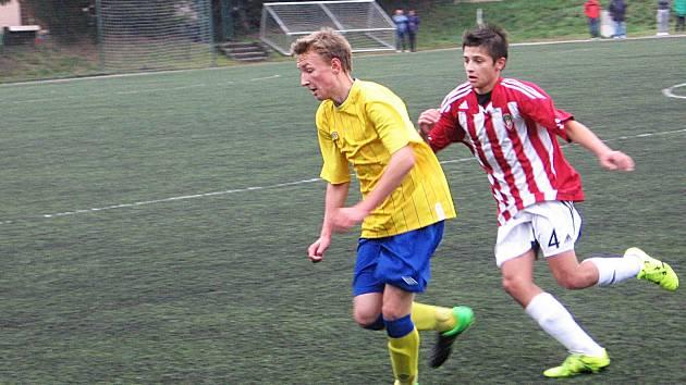 Benešovský Petr Srb (ve žlutém) běží za míčem pronásledován žižkovským Michalem Kubrem.