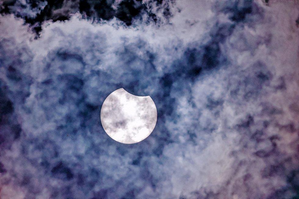 Detail částečného zatmění Slunce přes mraky.